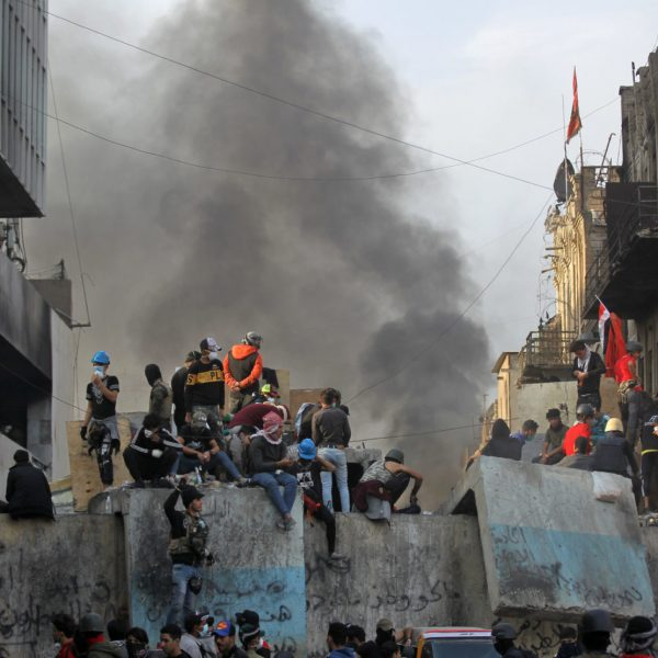 Iraqi demonstrators sit on a barrier amid clashes with security forces in the capital Baghdad's al-Rasheed street near al-Ahrar bridge, on November 27, 2019, during ongoing anti-government demonstrations. - Two protesters were shot dead in Baghdad and other Iraq cities were shrouded in acrid smoke from burning tyres as demonstrators pressed their campaign of anti-government rallies. Masked youths sealed off streets with makeshift barricades across the restive south as schools and public offices stayed shut. (Photo by AHMAD AL-RUBAYE / AFP)