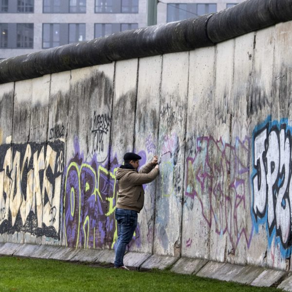 A man looks through a crack in a segment of the Berlin wall at the Berlin Wall memorial, after official guests attended celebrations of the 30th anniversary of the fall of the Berlin Wall, on November 9, 2019 in Bernauer Strasse in Berlin. - Germany celebrates 30 years since the fall of the Berlin Wall ushered in the end of communism and national reunification, as the Western alliance that secured those achievements is increasingly called into question. (Photo by John MACDOUGALL / AFP)