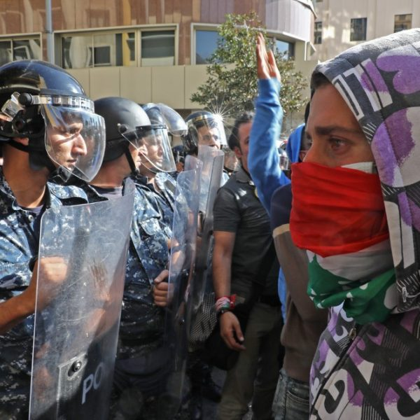 Lebanese protesters stand before with security forces near the parliament headquarters in the capital Beirut's downtown district on November 19, 2019. - An unprecedented protest movement against the ruling elite entered its second month with the country in the grip of political and economic turmoil. The leaderless pan-sectarian movement has swept the Mediterranean country since October 17, prompting the resignation of Prime Minister Saad Hariri's government. (Photo by Anwar AMRO / AFP)