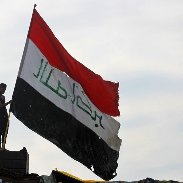 An Iraqi demonstrator waves a large national flag in the capital Baghdad's Tahrir Square, amid ongoing anti-government protests, on December 6, 2019. - Tahrir has become a melting pot of Iraqi society, occupied day and night by thousands of demonstrators angry with the political system in place since the aftermath of the US-led invasion of 2003 and Iran's role in propping it up. (Photo by AHMAD AL-RUBAYE / AFP)