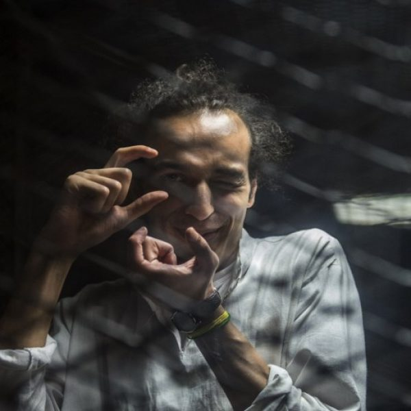 Egyptian photographer Mahmoud Abdel Shakour, known as Shawkan, gestures from inside a soundproof glass dock, during his trial in  the capital Cairo on August 9, 2016, Shawkan had been covering the police dispersal of an Islamist protest camp in Cairo when he was arrested and has been in prison ever since. Thousands of Islamists remain in prison in a wideranging crackdown that has extended to leftists and even journalists like Shawkan./ AFP PHOTO / KHALED DESOUKI / TO GO WITH AFP STORY BY HAITHAM EL-TABEI