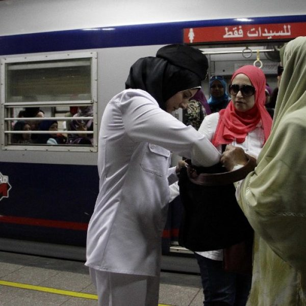 An Egyptian policewoman inspects commuters' bags at the