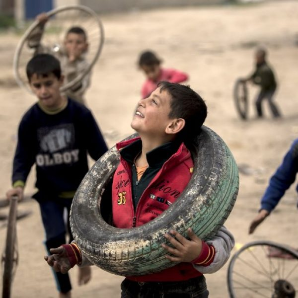 Palestinian children play outdoors with discarded tires and rims, near the Gaza strip's sole electricity plant, on February 15, 2018, after it stopped working at midnight the previous night due to lack of fuel. The sole electricity plant in the Gaza Strip stopped working Thursday because of a lack of fuel, officials said, as concerns grew over worsening humanitarian conditions in the Palestinian enclave. / AFP PHOTO / MOHAMMED ABED